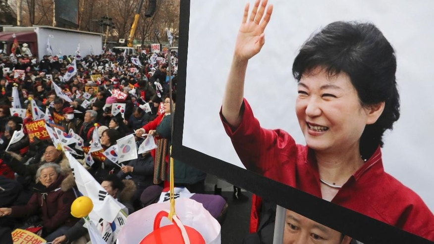 A supporter holds a picture of South Korean President Park Geun-hye as others hold their national flags during a rally opposing her impeachment in Seoul, South Korea, Saturday, Dec. 31, 2016. The Constitutional Court has up to six months to decide whether Park should permanently step down over a corruption scandal or be reinstated. (AP Photo/Lee Jin-man)