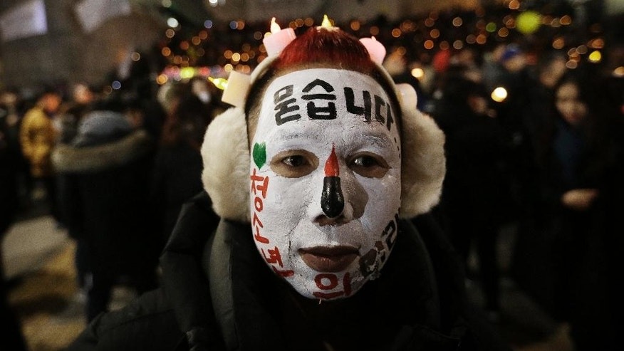 "A protester with his face painted attends a candle light vigil calling for impeached President Park Geun-hye to step down in Seoul, South Korea, Saturday, Dec. 31, 2016. Even on New Year's Eve, large crowds of South Koreans gathered to join another rally demanding the ouster of impeached President Park Geun-hye, who's determined to restore her powers through a court trial. The letters read "" Asking"". (AP Photo/Ahn Young-joon)"