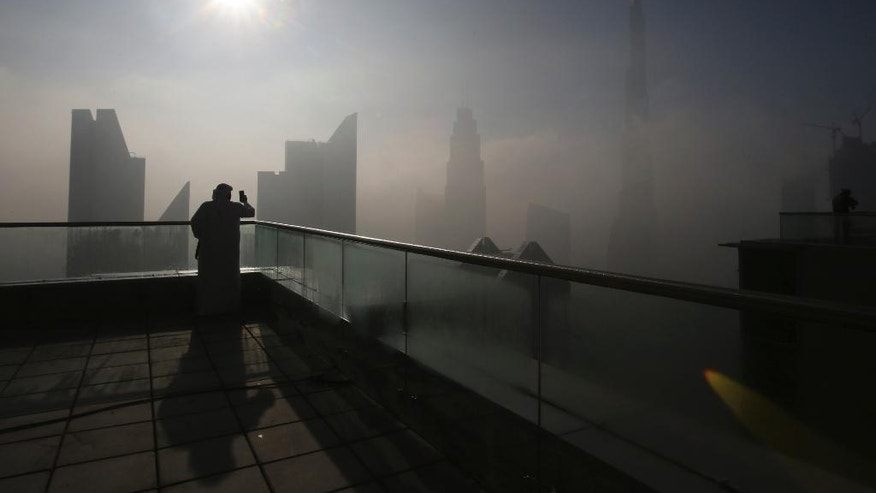 A man takes photos of the Burj Khalifa, world's tallest tower, on a foggy day in Dubai, United Arab Emirates, Friday, Dec. 30, 2016. (AP Photo/Kamran Jebreili)