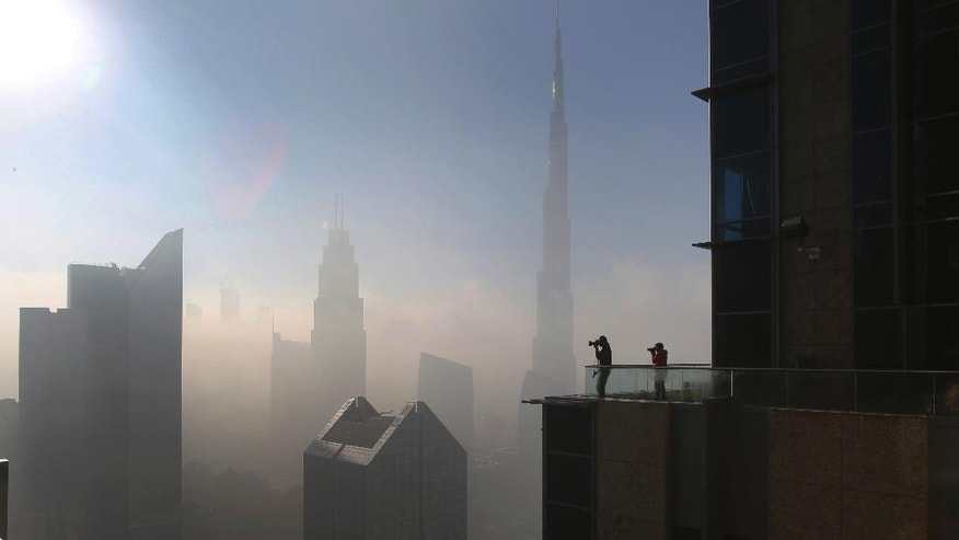 People take pictures at balcony on the 42nd floor of a building on a foggy day in Dubai, United Arab Emirates, Friday, Dec. 30, 2016. (AP Photo/Kamran Jebreili)