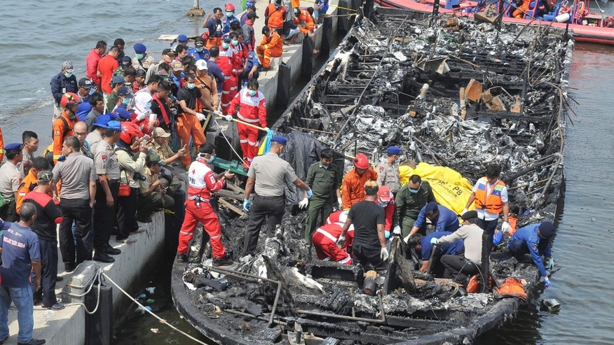 Rescuers search for victims from the wreckage of a ferry that caught fire off the coast of Jakarta after it was docked at Muara Angke Port in Jakarta, Indonesia, Sunday,  Jan. 1, 2017. The vessel was carrying more than 230 people from the port to Tidung, a resort island in the Kepulauan Seribu chain, when it caught fire, officials said. (AP Photo/Rhana Ananda)