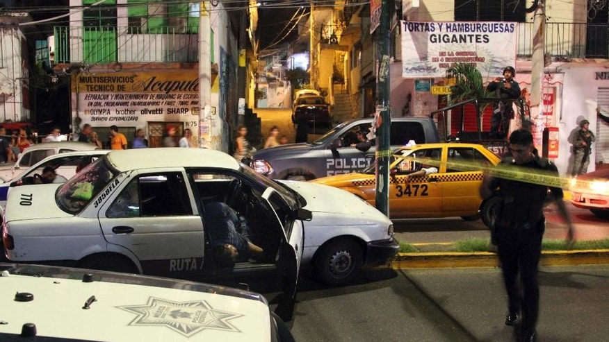 A taxi driver lies dead in his car after being shot shortly before midnight in a busy street in Acapulco early Sunday, Jan. 1, 2017. At least five people were killed over the New Year's weekend in the Mexican resort city of Acapulco, including three men found decapitated in a central neighborhood.(AP Photo/Bernandino Hernandez)