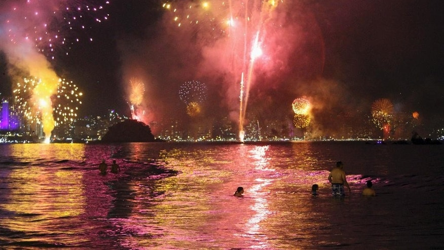 Fireworks explode over the Acapulco bay during a New Year's Eve celebration in Acapulco, Mexico, Sunday, Jan. 1, 2017. At least five people were killed over the New Year's weekend in the Mexican resort city of Acapulco, including three men found decapitated in a central neighborhood.(AP Photo/Bernandino Hernandez)