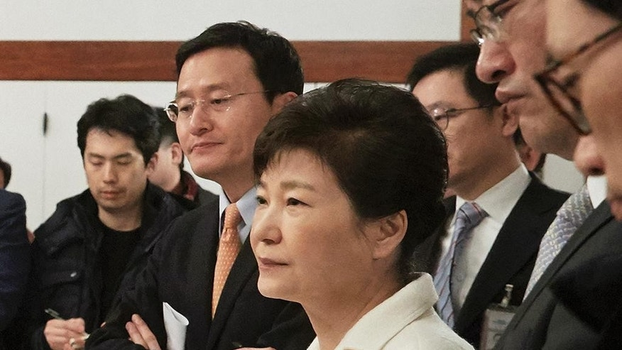 In this photo provided by the South Korean Presidential House, impeached South Korean President Park Geun-hye, center, listens to a reporter's  question during a meeting with a selected group of reporters at the presidential house in Seoul, South Korea, Sunday, Jan. 1, 2017. Park vehemently rejected accusations Sunday that she conspired with a longtime friend to extort money and favors from companies, accusing her opponents of framing her. (The South Korean Presidential House via AP)