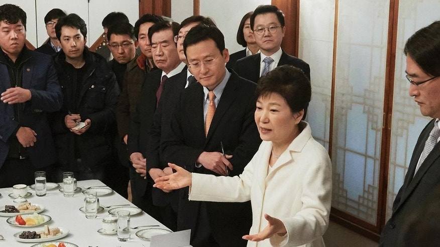 In this photo provided by the South Korean Presidential House, impeached South Korean President Park Geun-hye, second from right, speaks during a meeting with a selected group of reporters at the presidential house in Seoul, South Korea, Sunday, Jan. 1, 2017. Park vehemently rejected accusations Sunday that she conspired with a longtime friend to extort money and favors from companies, accusing her opponents of framing her. (The South Korean Presidential House via AP)