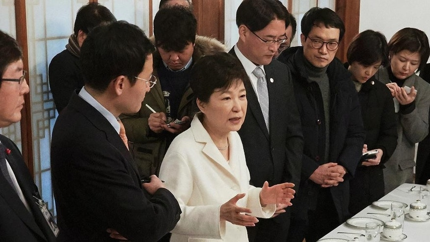 In this photo provided by the South Korean Presidential House, impeached South Korean President Park Geun-hye, third from left, speaks during a meeting with a selected group of reporters at the presidential house in Seoul, South Korea, Sunday, Jan. 1, 2017. Park vehemently rejected accusations Sunday that she conspired with a longtime friend to extort money and favors from companies, accusing her opponents of framing her. (The South Korean Presidential House via AP)