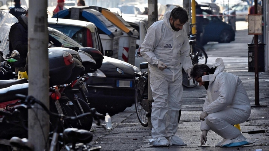 Forensic police collect evidence on the site of the explosion of a bomb in front of a bookstore in Florence, Italy, Sunday, Jan. 1, 2017. A bomb-squad officer was wounded when a suspicious package he was examining exploded. (Maurizio Degl'Innocenti/ANSA via AP)