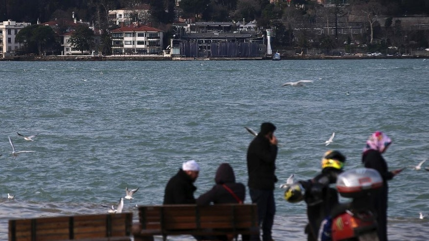 People go about their lives on the Asian side of Istanbul, with the nightclub by the Bosphorus, top centre, which was attacked by a gunman overnight,  is seen in Istanbul, on New Year's Day, Sunday, Jan 1, 2017. An assailant believed to have been dressed in a Santa Claus costume and armed with a long-barrelled weapon, opened fire at the nightclub in Istanbul's Ortakoy district during New Year's celebrations, killing dozens of people and wounding dozens of others in what the province's governor described as a terror attack. (AP Photo/Emrah Gurel)