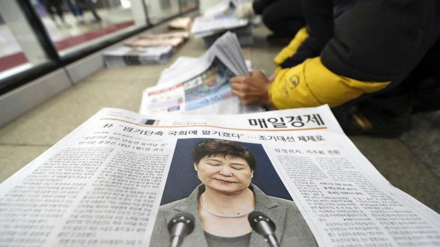 FILE - In this Nov. 29, 2016 file photo, a worker prepares to deliver newspapers reporting on South Korean President Park Geun-hye's public announcement at a distribution station in Seoul, South Korea. South Korean prosecutors said Monday, Jan. 2, 2017. the daughter of Choi Soon-sil, the confidante of disgraced president, has been arrested in Denmark and authorities are working to get her returned home in connection with a huge corruption scandal. (AP Photo/Lee Jin-man, File)