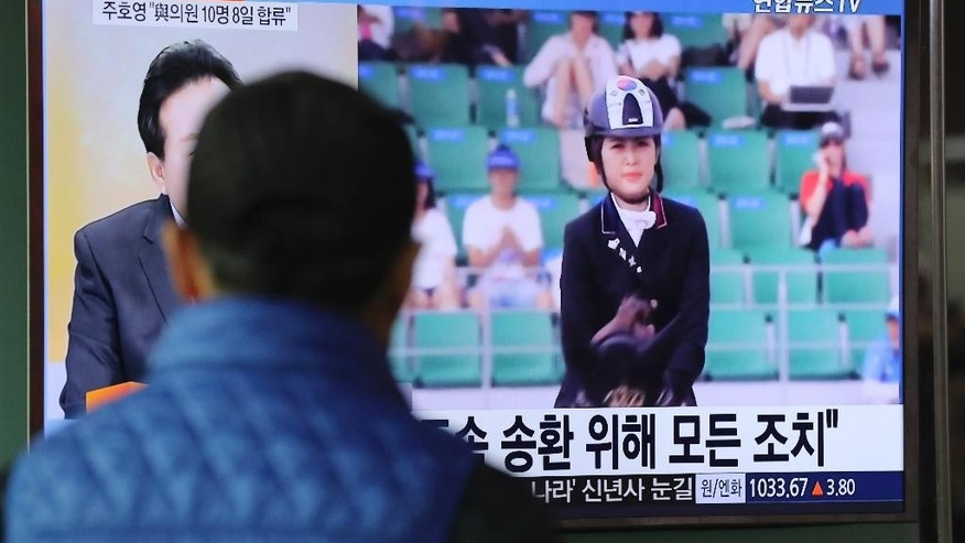 A man watches a TV screen showing the news program about Chung Yoo-ra, the daughter of the Choi Soon-sil who the confidante of disgraced President Park Geun-hye, at the Seoul Railway Station in Seoul, South Korea, Monday, Jan. 2, 2017. South Korean prosecutors said Monday the daughter of the confidante of disgraced President Park has been arrested in Denmark and authorities are working to get her returned home in connection with a huge corruption scandal. (AP Photo/Lee Jin-man)