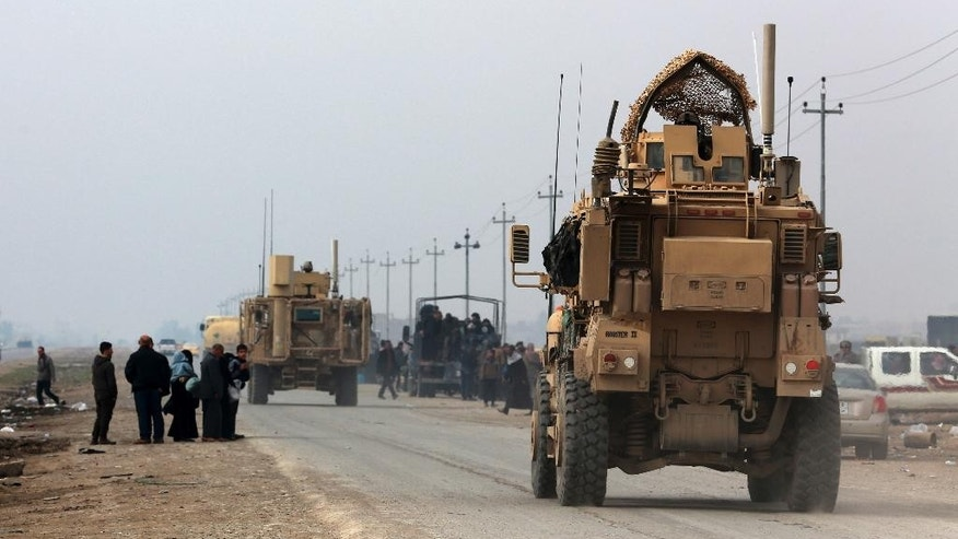 U.S. Army armoured vehicles travel in Bartella, around 19 miles (30 kilometers), from Mosul, Iraq, Saturday, Dec 31, 2016. (AP Photo/ Khalid Mohammed)