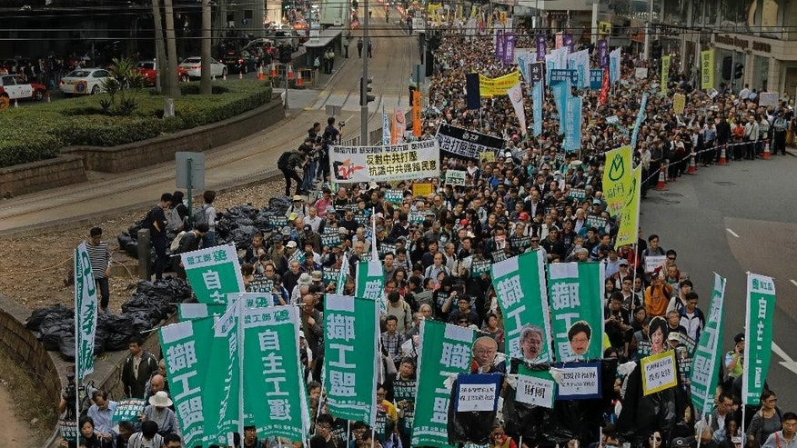 Thousands of people march on the first day of 2017 at a downtown street in Hong Kong Sunday, Jan. 1, 2017, to protest against Beijing's interpretation of Basic Law and Hong Kong government's bid to ban pro-democracy lawmakers from taking office. They also demand true universal suffrage, which is not happening in the coming chief executive election in March. (AP Photo/Vincent Yu)