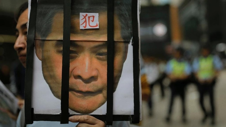 "A protester raises a picture of Chief Executive Leung Chun-ying with a Chinese word ""Prisoner"" on his face during a rally on the first day of 2017 in Hong Kong, Sunday, Jan. 1, 2017. They protest against Beijing's interpretation of Basic Law and Hong Kong government's bid to ban pro-democracy lawmakers from taking office. They also demand true universal suffrage, which is not happening in the coming chief executive election in March. (AP Photo/Vincent Yu)"