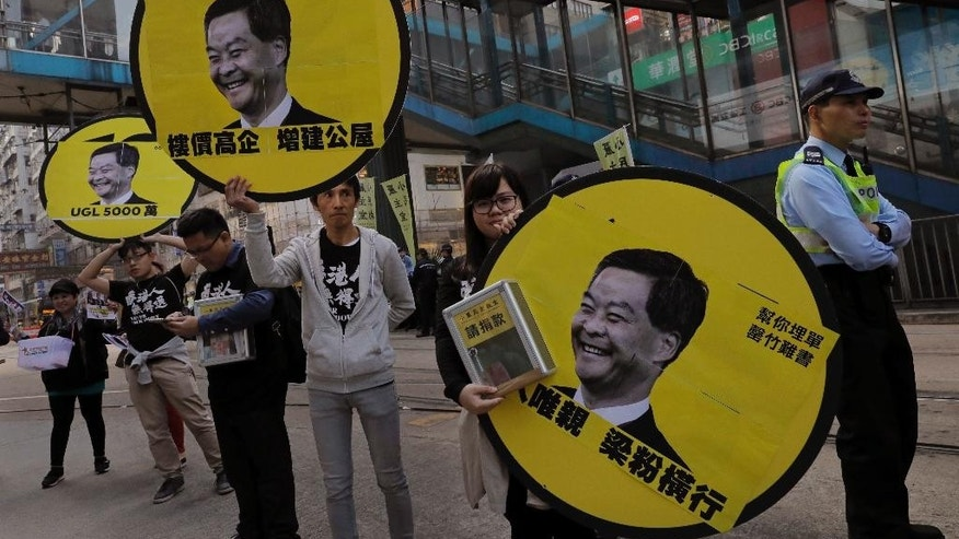 Protesters raise pictures of Chief Executive Leung Chun-ying during a protest on the first day of 2017 in Hong Kong, Sunday, Jan. 1, 2017. They protest against Beijing's interpretation of Basic Law and Hong Kong government's bid to ban pro-democracy lawmakers from taking office. They also demand true universal suffrage, which is not happening in the coming chief executive election in March. (AP Photo/Vincent Yu)