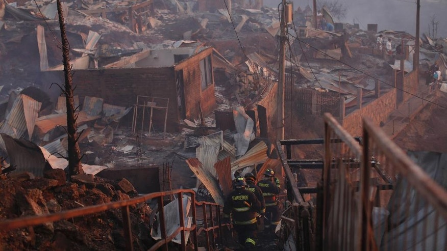 Firefighters walk down a ladder while working to control a fire in Valparaiso, Chile, Monday, Jan. 2, 2017.  The fire, driven by strong winds, swept through forest land in the hills outside the Chilean port of Valparaiso, destroying dozens of homes, sending a pall of heavy smoke down onto the city and driving the authorities to evacuate hundreds of people. (AP Photo / Luis Hidalgo)