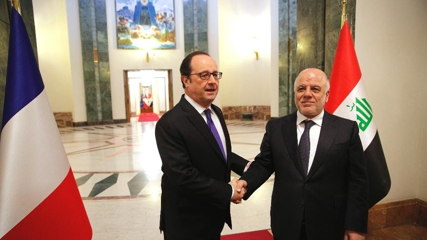 Iraq's Prime Minister Haider al-Abadi, right, greets French President Francois Hollande prior to their meeting in Baghdad, Iraq, Monday, Jan. 2, 2017. Hollande is in Iraq for a one-day visit. (AP Photo/Christophe Ena, Pool)