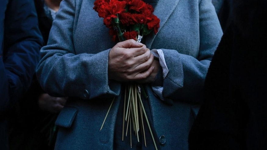 A Turkish woman holds carnations at a security barricade near the scene, a day after an attack at a popular nightclub in Istanbul, Monday, Jan. 2, 2017. A manhunt is on in Turkey as authorities work to identify the assailant who killed dozens of people in a crowded Istanbul nightclub during New Year's celebrations Sunday. (AP Photo/Emrah Gurel)