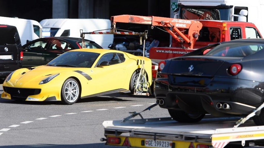FILE - In this Thursday, Nov. 3, 2016 file picture, two Ferrari sports cars are being towed off the freight zone by the police at Geneva Airport, in Geneva, Switzerland. Geneva authorities have confiscated 11 luxury vehicles and sports cars Monday, belonging to Teodorin Obiang Nguema, the son of Equatorial Guinea's president as part of a preliminary investigation into alleged corruption. The son of Equatorial Guinea's president is going on trial in France for corruption, money laundering and embezzlement after a years-long investigation. (Laurent Gillieron/Keystone via AP, File)