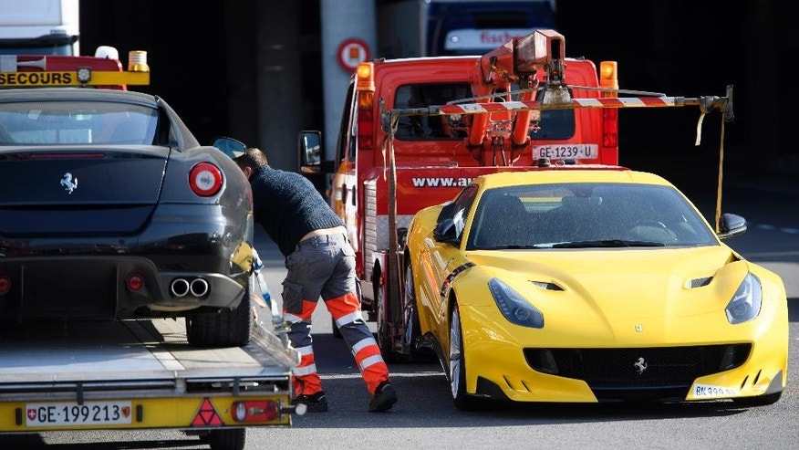 FILE - In this Thursday, Nov. 3, 2016 file picture, two Ferrari sports cars are being towed off the freight zone by the police at Geneva Airport, in Geneva, Switzerland. Geneva authorities have confiscated 11 luxury vehicles and sports cars Monday, belonging to Teodorin Obiang Nguema, the son of Equatorial Guinea's president, as part of a preliminary investigation into alleged corruption. The son of Equatorial Guinea's president is going on trial in France for corruption, money laundering and embezzlement after a years-long investigation. (Laurent Gillieron/Keystone via AP, File)