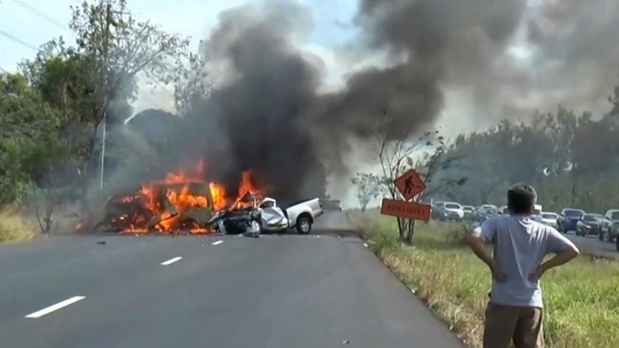 In this image made from video a man watches as two vehicles burn after they collided on a highway east of Bangkok, Thailand, Monday, Jan. 2, 2017. Authorities say a van and a pickup collided and caught fire on a highway in eastern Thailand, killing 25 people. The public transit van lost control and crossed the grass median, colliding with the pickup truck going in the opposite direction Monday afternoon, according to Thai Road Accident Data for Road Safety Culture, which compiles electronic insurance reports. (Matichon TV via AP)