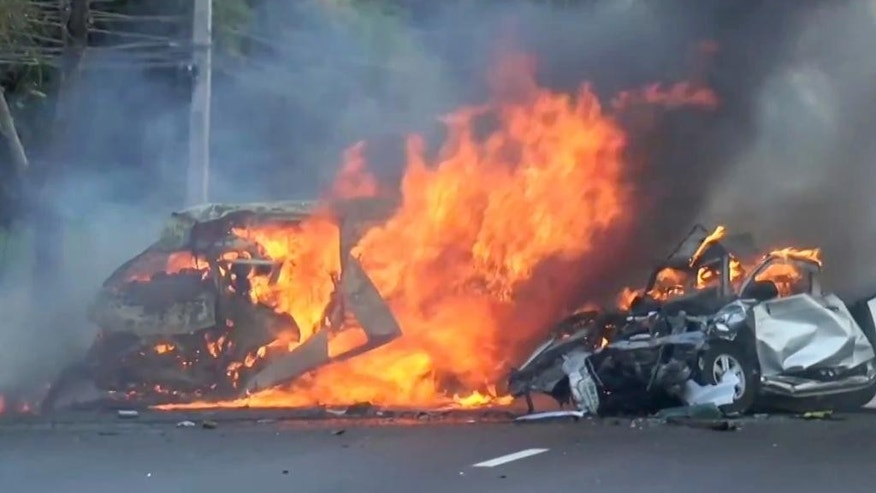 In this image made from video two vehicles burn after they collided on a highway east of Bangkok, Thailand, Monday, Jan. 2, 2017. Authorities say a van and a pickup collided and caught fire on a highway in eastern Thailand, killing 25 people. The public transit van lost control and crossed the grass median, colliding with the pickup truck going in the opposite direction Monday afternoon, according to Thai Road Accident Data for Road Safety Culture, which compiles electronic insurance reports. (Matichon TV via AP)