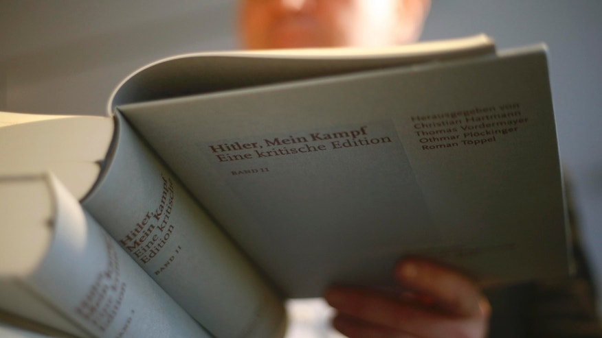 The owner of a book shop looks through a copy of the book 'Hitler, Mein Kampf. A Critical Edition' in Munich, Germany January 8, 2016. For the first time since Adolf Hitler's death, Germany is publishing the Nazi leader's political treatise 'Mein Kampf' ('My Struggle') unleashing a highly charged row over whether the text is an inflammatory racist diatribe or a useful educational tool.  REUTERS/Michael Dalder  TPX IMAGES OF THE DAY   - RTX21IHC