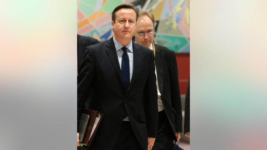 FILE - In this file photo dated Thursday, Dec. 18, 2014, British Prime Minister David Cameron, left, walks with Britain's permanent representative to European Union Ivan Rogers, right,  at the European Council building in Brussels.  The British Foreign Office announced Tuesday Jan. 3, 2017, that Rogers has resigned, without giving any details about his departure. (AP Photo/Yves Logghe, FILE)