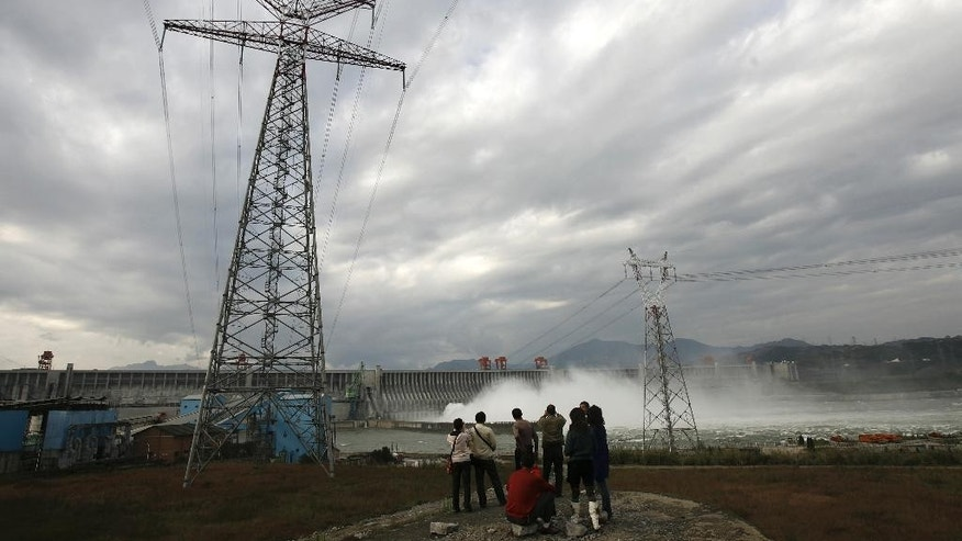 In this Nov. 7, 2008 photo, people stand near electric pylons watching flow of water is discharged through the Three Gorges Dam in Yichang in central China's Hubei province. Three Gorges Group is spending heavily to buy or build hydro, wind and solar projects at a time when Western utility investors are pulling back and U.S. President-elect Donald Trump's pledge to revive coal use has raised doubt about U.S. support for renewables. (Chinatopix via AP)