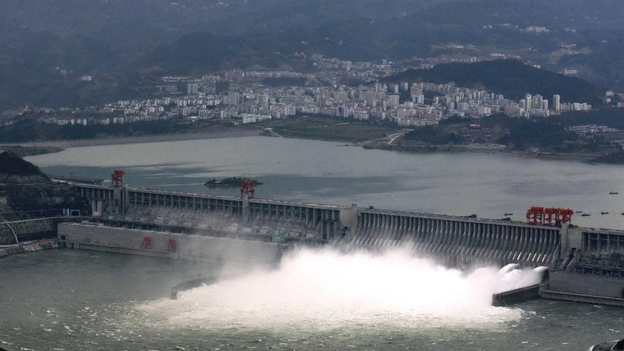In this Nov. 7, 2008 photo, flow of water is discharged through the Three Gorges Dam in Yichang in central China's Hubei province. State-owned China Three Gorges Group is spending heavily to buy or build hydro, wind and solar projects at a time when Western utility investors are pulling back and U.S. President-elect Donald Trump's pledge to revive coal use has raised doubt about U.S. support for renewables. (Chinatopix via AP)