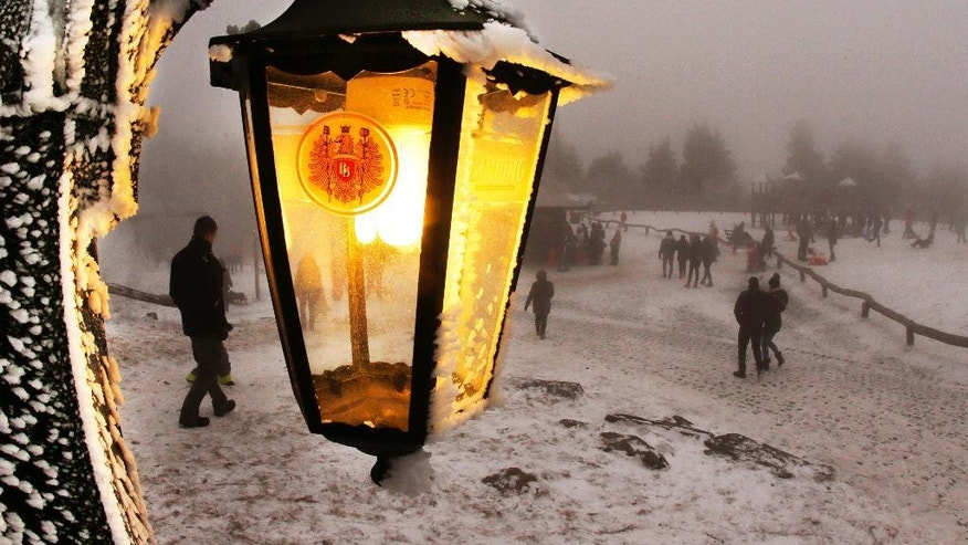 A lamp of a restaurant shines as trippers walk by in thick fog on top of the 880 m high Feldberg mountain near Frankfurt, Germany, Monday, Jan. 2, 2017. (AP Photo/Michael Probst)