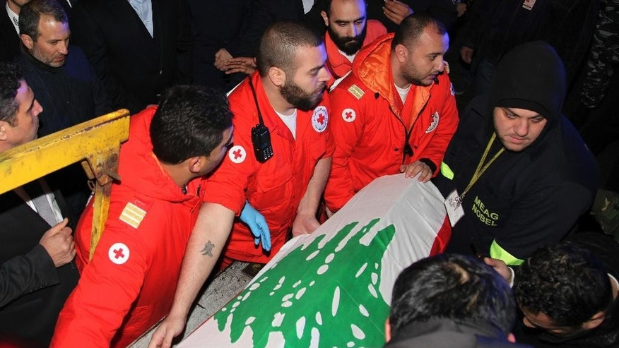 In this photo released by the Lebanese Government, Lebanese Red Cross volunteers unload the coffin of a Lebanese victim who was killed in the Istanbul nightclub attack, at Rafik Hariri international airport, in Beirut, Lebanon, Monday Jan. 2, 2017. A jet carrying the bodies of three Lebanese citizens killed in the shooting at an Istanbul nightclub has landed in Beirut, with three others who were wounded aboard. The jet arrived Monday night from Istanbul where 39 people died in the New Year Eve's attack. (Dalati Nohra/Lebanese Government via AP)