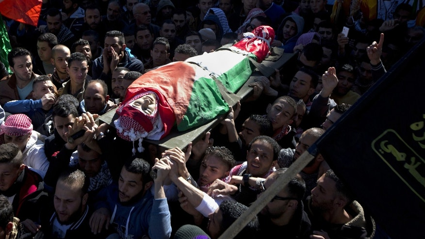 Palestinian mourners carry the body of Malik Shaheen, 21, who was killed in clashes with Israeli troops, during his funeral.
