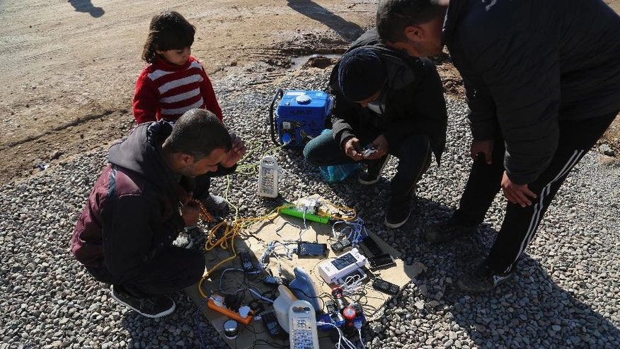 Displaced Iraqis, who fled fighting between Iraqi security forces and Islamic State militants, wait to charge their mobile phones and electrical lanterns, the generator owner charging 500 Iraqi dinars (about 45 U.S. cents) to charge each mobile phone, at Sewdinan Camp for the displaced near Khazer, Iraq on Tuesday, Jan. 3, 2017. Displaced by the fighting in Mosul, Iraqis who escaped Islamic State rule in the northern Iraqi city are doing something they had not done in more than two years: Speaking publicly on their mobile phones and using social media to communicate with friends, relatives and loved ones (AP Photo/ Khalid Mohammed)