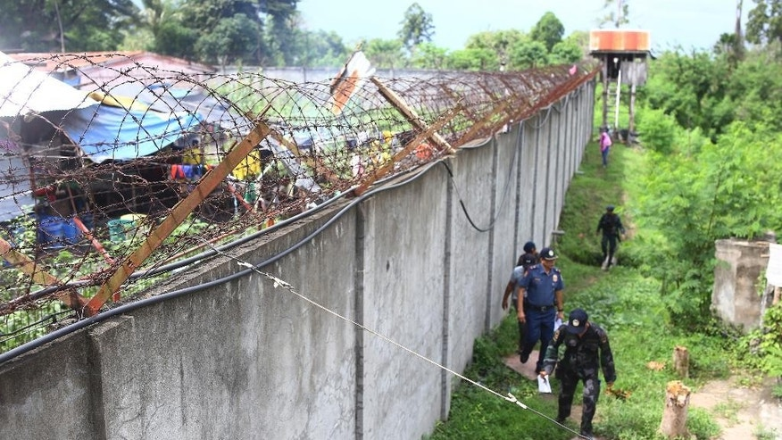 Policemen patrol outside the walls of the North Cotabato District Jail in Kidapawan city, Cotabato Province, southern Philippines, after a massive jailbreak early Wednesday, Jan. 4, 2017. In one of the country's largest jailbreaks in recent years, nearly 160 inmates escaped after suspected Muslim rebels attacked the jail before dawn Wednesday killing at least six people as pursuing government forces traded fire with gunmen, officials said. (AP Photo)