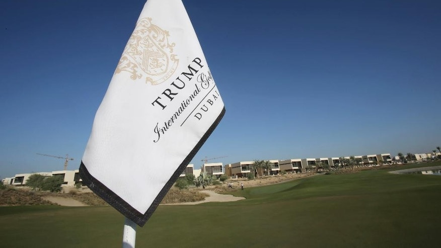 In this Tuesday, Dec. 20, 2016 photo, a flag flies on a green lined with villas at the Trump International Golf Club, in Dubai, United Arab Emirates. The 18-hole golf course in Dubai bearing Donald Trump's name exemplifies the questions surrounding his international business interests. The course will open in February 2017 in the United Arab Emirates, but concerns about security, financial agreements and other matters have yet to be answered by the incoming 45th American president. (AP Photo/Kamran Jebreili)