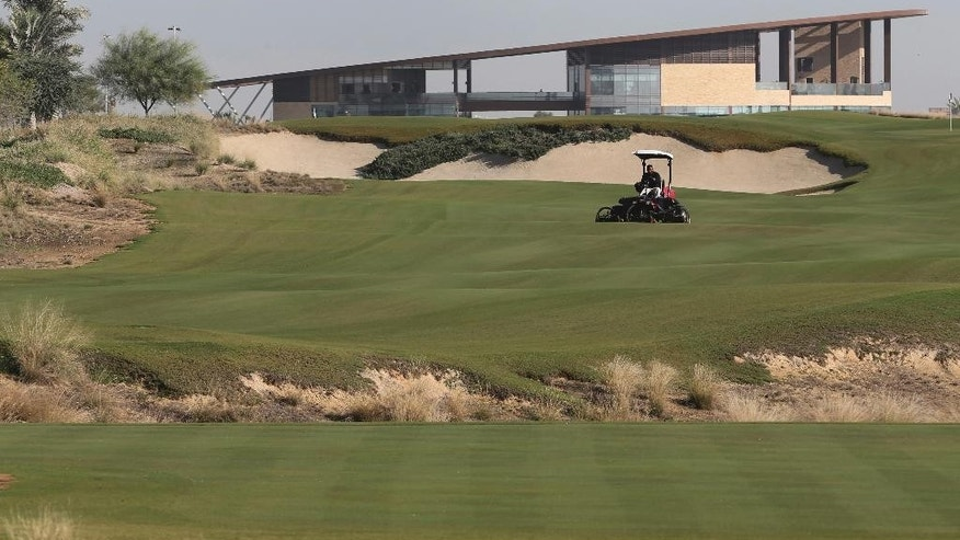 In this Tuesday, Dec. 20, 2016 photo, an employee mows the grass in front of the clubhouse at the Trump International Golf Club, in Dubai, United Arab Emirates. The 18-hole golf course in Dubai bearing Donald Trump's name exemplifies the questions surrounding his international business interests. The course will open in February 2017 in the United Arab Emirates, but concerns about security, financial agreements and other matters have yet to be answered by the incoming 45th American president. (AP Photo/Kamran Jebreili)