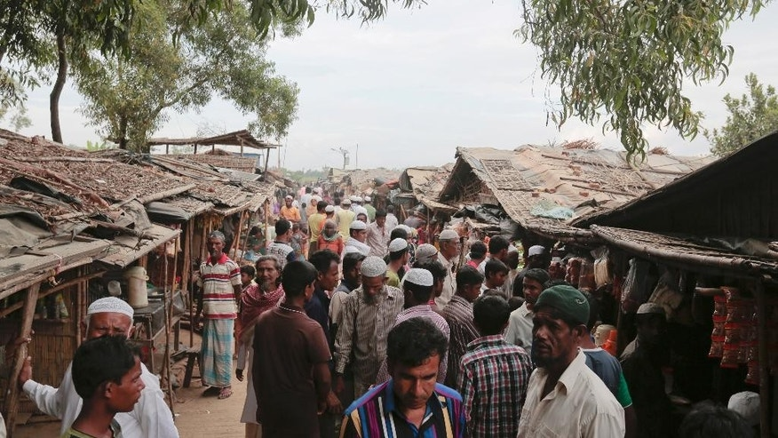 FILE - In this Dec. 2, 2016, file photo, Rohingya from Myanmar make their way in an alley at an unregistered refugee camp in Teknaf, near Cox's Bazar, a southern coastal district about, 296 kilometers (183 miles) south of Dhaka, Bangladesh. Newly revealed video of Myanmar police beating Rohingya Muslims in northern Rakhine state has weakened months of government claims that its forces have not committed abuses in the region since a deadly insurgent attack in October. The footage has made it more difficult for the government to say at least some abuses are not happening and sown doubts into its dismissals of more grievous allegations. (AP Photo, File)