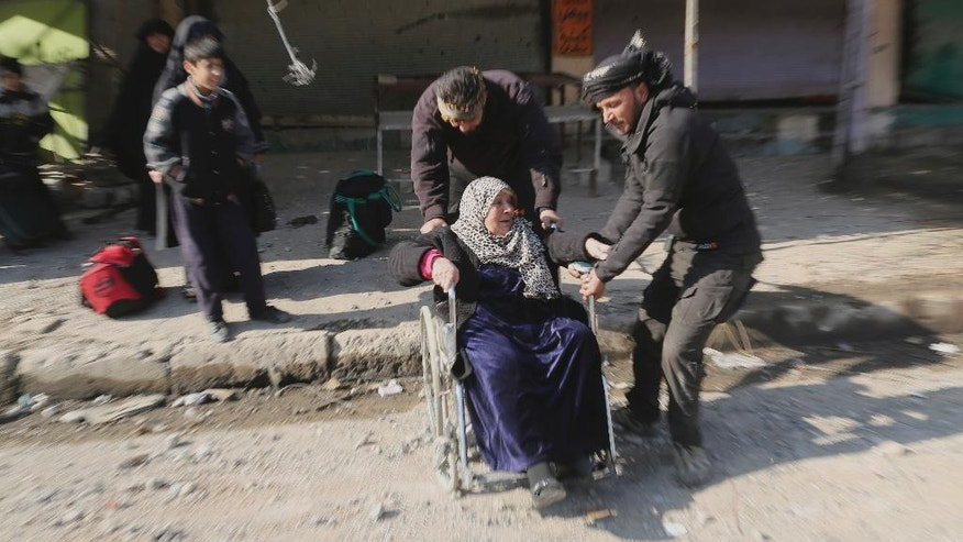 Soldiers of Iraq's elite counterterrorism forces help an elderly woman as she and her family flee  fighting between Iraqi security forces against Islamic State militants, in Mosul, Iraq, Monday, Jan. 2, 2017. (AP Photo/Khalid Mohammed)