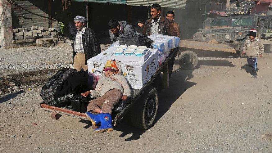 Residents bring food to their families after being trapped for days in their homes due to fighting between Iraqi security forces and Islamic State militants, in Mosul, Iraq, Monday, Jan. 2, 2017. (AP Photo/ Khalid Mohammed)