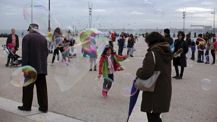A child laughs as she tries to catch soap bubbles created by a street artist, in Lisbon's Comercio square, Tuesday, Jan. 3 2017. (AP Photo/Armando Franca)