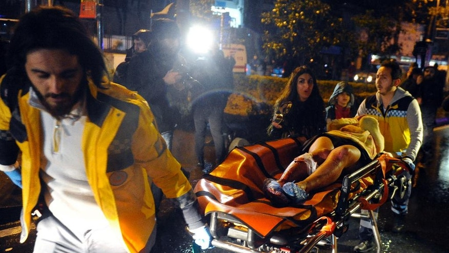 FILE - In this Sunday, Jan. 1, 2017 file photo, medics carry a wounded person at the scene after an attack at a popular nightclub in Istanbul. Survivors of the massacre at a Turkish nightclub describe an hour of pure terror and how they escaped, by feigning death, rappelling to the sea, or hiding anywhere they could find. The Islamic State gunman fired 180 rounds for seven minutes, killing 39 people on New Year's Eve. He escaped after he wiped his Kalashnikov free of fingerprints, changed clothes, put on a Santa hat and blended into the crowd evacuating the bloody Reina nightclub. (IHA via AP, File)