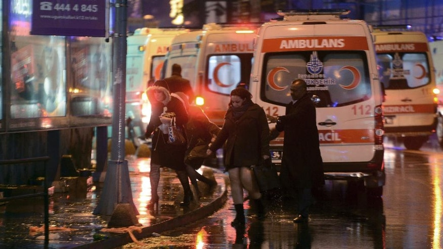 FILE - In this Sunday, Jan. 1, 2017 file photo, people leave as medics and security officials work at the scene after an attack at a popular nightclub in Istanbul. Survivors of the massacre at a Turkish nightclub describe an hour of pure terror and how they escaped, by feigning death, rappelling to the sea, or hiding anywhere they could find. The Islamic State gunman fired 180 rounds for seven minutes, killing 39 people on New Year's Eve. He escaped after he wiped his Kalashnikov free of fingerprints, changed clothes, put on a Santa hat and blended into the crowd evacuating the bloody Reina nightclub. (IHA via AP, File)