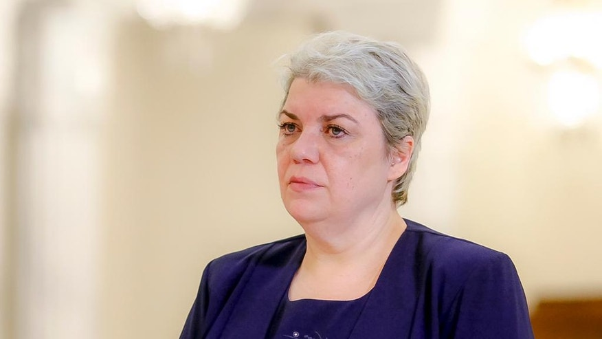 FILE - In this May 20, 2015 file photo, Sevil Shhaideh, 52, stands at the Romanian presidency before being sworn in as regional development minister in Bucharest, Romania. Shhaideh, who had been poised to become the country's first female and Muslim prime minister was offered a job as deputy premier Tuesday, Jan. 3, 2017 after the country's president declined to nominate her for the top government job.  (AP Photo/Octav Ganea, file)