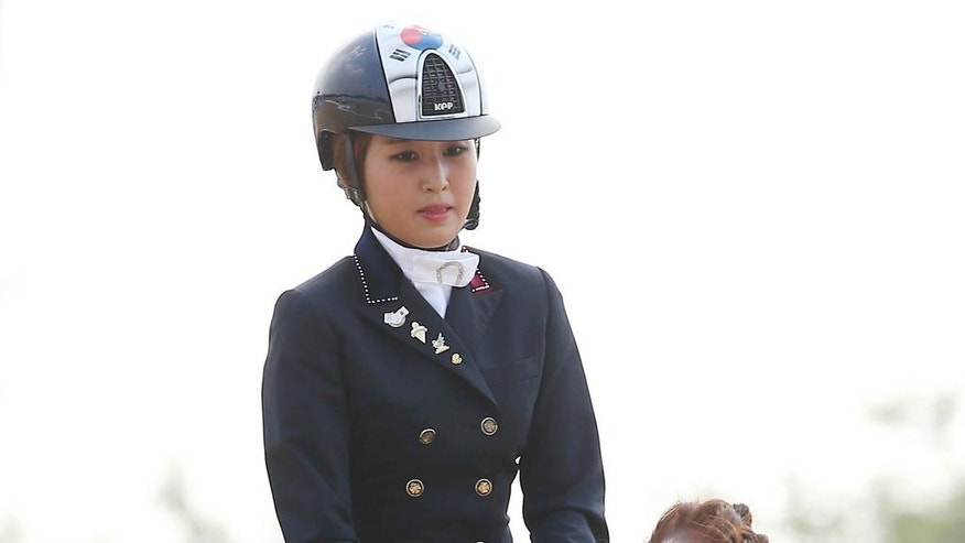 In this photo taken on Sept. 20, 2014, South Korea's Chung Yoo-ra, the daughter of Choi Soon-sil, the confidante of disgraced President Park Geun-hye, competes during the equestrian dressage team competition for the 17th Asian Games in Incheon, South Korea. South Korean prosecutors said Monday, Jan. 2, 2017, Chung has been arrested in Denmark and authorities are working to get her returned home in connection with a huge corruption scandal. (Lee Sang-hak/Yonhap via AP)