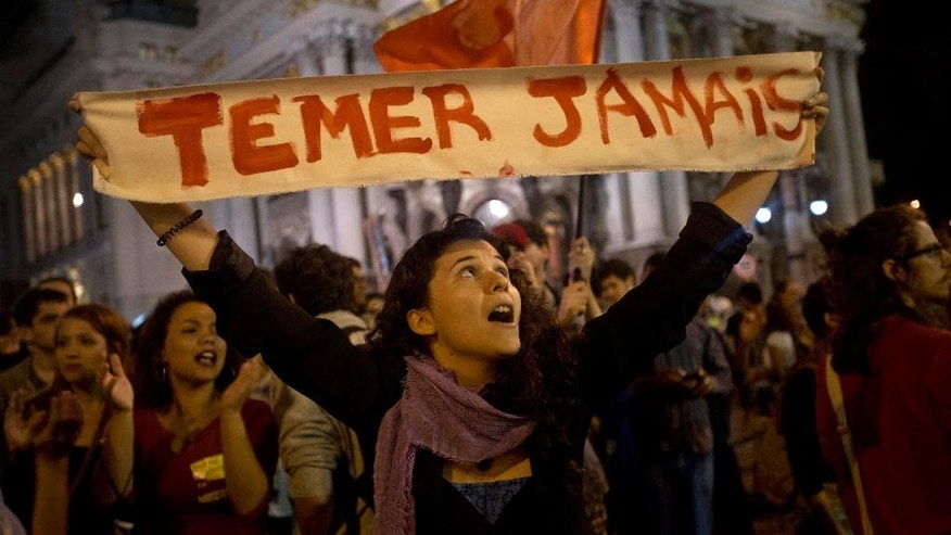 "FILE - In this May 13, 2016 file photo, a woman holds a sign that reads in Portuguese; ""Never Temer!"" to protest the government of acting President Michel Temer in Rio de Janeiro, Brazil. Even without the mishaps, Temer, a 75-year-old career politician who took over when President Dilma Rousseff was ousted last year, is facing myriad challenges that threaten his ability to remain in power. (AP Photo/Silvia Izquierdo)"