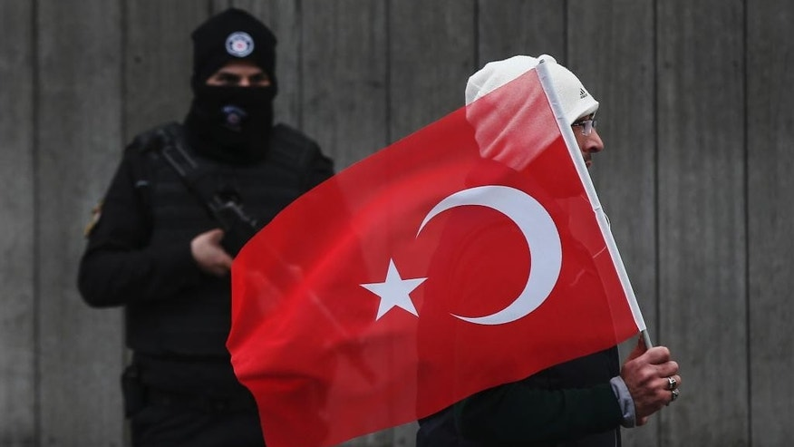 "A man with a Turkish flag walks past a Turkish police officer guarding the scene, during a memorial outside the Reina club following the New Year's day attack, in Istanbul, Turkey, Tuesday, Jan. 3, 2017.  The Islamic State group claimed responsibility for the attack killing 39 people saying a ""soldier of the caliphate"" had carried out the mass shooting to avenge Turkish military operations against IS in northern Syria. (AP Photo/Emrah Gurel)"