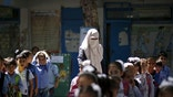 A veiled Palestinian teacher stands next to children as they queue at a United Nations Relief and Work Agency (UNRWA)-run school in Gaza September 22, 2015. As the United Nations celebrates its 70-year anniversary this year, Reuters documents the work of the organisation's main aid agency in the Gaza Strip, the United Nations Relief and Works Agency (UNRWA). The agency runs schools including the al-Nour (Light) School for the Blind and Visually Impaired Children in Gaza City and has helped families to repair their homes or find temporary alternatives following the 2014 Gaza conflict. UNRWA said in January that a lack of international funding forced it to suspend cash payments for repairs to homes. The enclave has been under Israeli blockade for years and the two sides have waged two other wars since Hamas took control of Gaza in 2007. The agency is mostly funded by voluntary contributions and has struggled to keep pace with demand for its services, the U.N. said in August. Picture taken September 22, 2015. REUTERS/Mohammed Salem - RTS5LAO