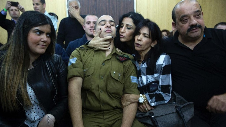 File - In this Wednesday, Jan. 4, 2017 file photo, Israeli solider Sgt. Elor Azaria waits with his parents for the verdict inside the military court in Tel Aviv, Israel on. The Israeli military, which has battled foes on all of the country's borders, is now facing a challenge from within: nationalist politicians who are increasingly criticizing the army and bickering with Israel's security establishment. Angry reactions from within Prime Minister Benjamin Netanyahu's coalition to the manslaughter conviction this week of an Israeli soldier who fatally shot an already wounded Palestinian underscored the growing rift. Netanyahu and other senior Cabinet ministers quickly called for the soldier to be pardoned, in effect undercutting the authority of the military court that convicted the young man.( Heidi Levine, Pool via AP, File).