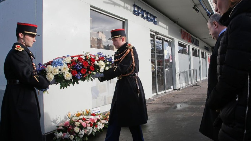 French Interior Minister Bruno Leroux, left, and State Secretary in charge of Victims Juliette Meadel, right, attend a ceremony at the place of the terrorist attack at the kosher supermarket.