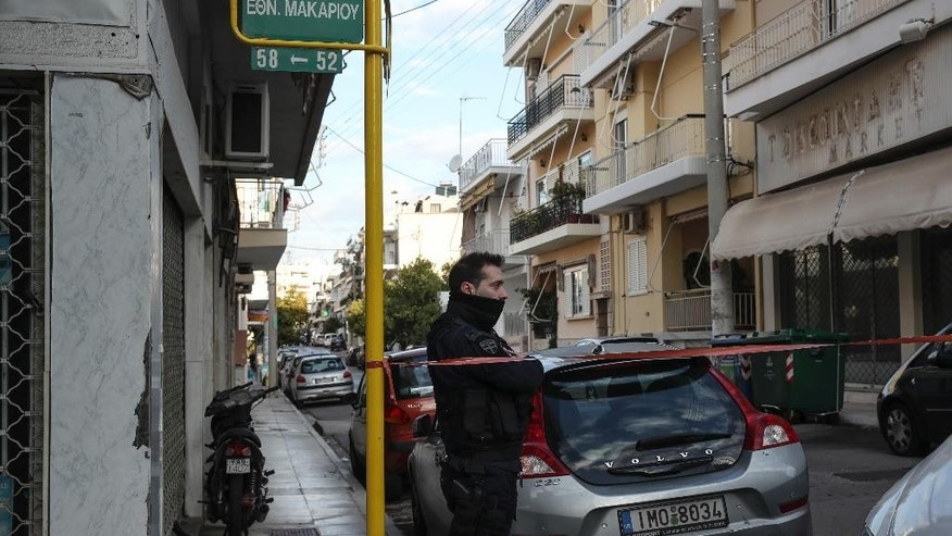 A policeman secures a street where police conducts an investigation at a suburb of Athens, Thursday, Jan. 5, 2017. Greek police say they have recaptured a convicted far-left militant wanted for more than four years after she absconded during her trial on domestic terrorism charges. (AP Photo/Yorgos Karahalis )